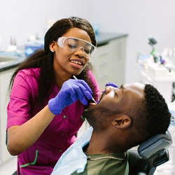 dentist cleaning patient's mouth