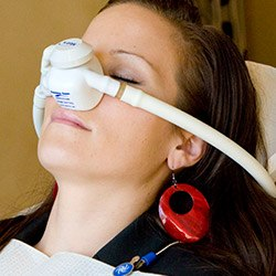Woman with nitrous oxide mask in dental chair