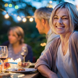 person smiling at a dinner party